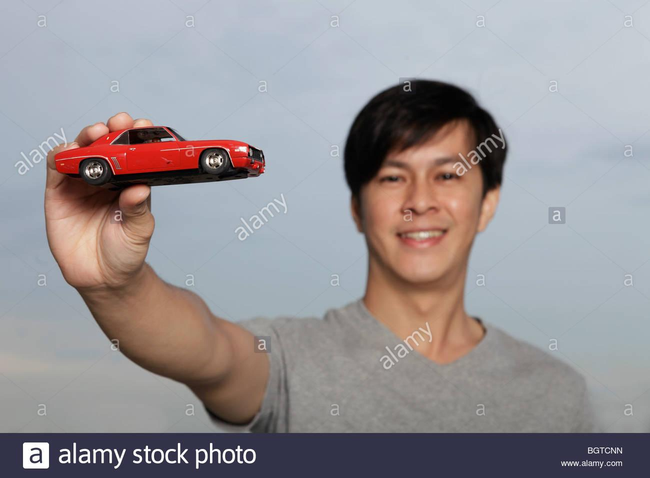 young-man-holding-up-red-toy-car-BGTCNN.jpg